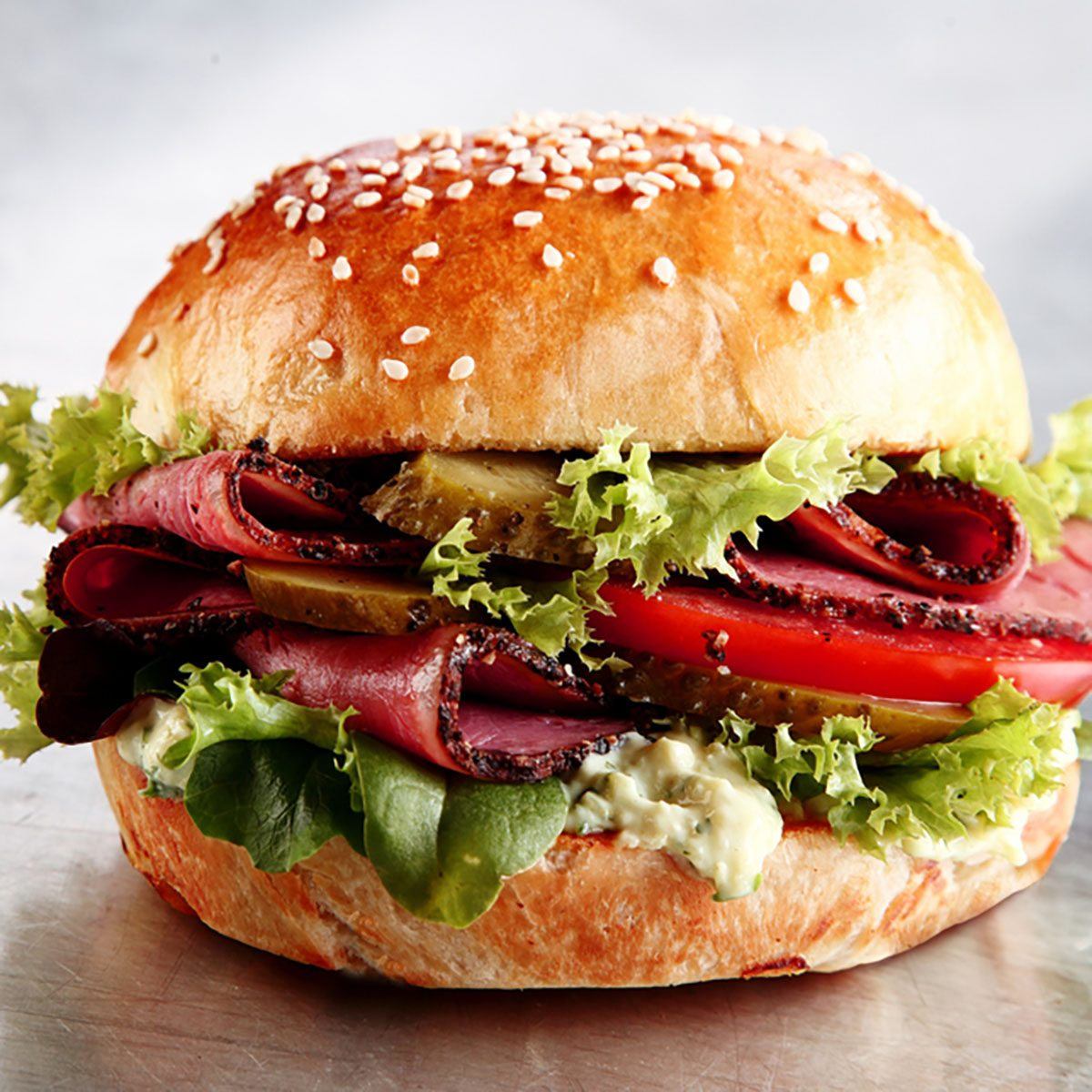 Delicious sesame bun with sliced roast beef or pastrami with lettuce, tomato, gherkin, and mayo on a silver counter in a cafeteria or restaurant