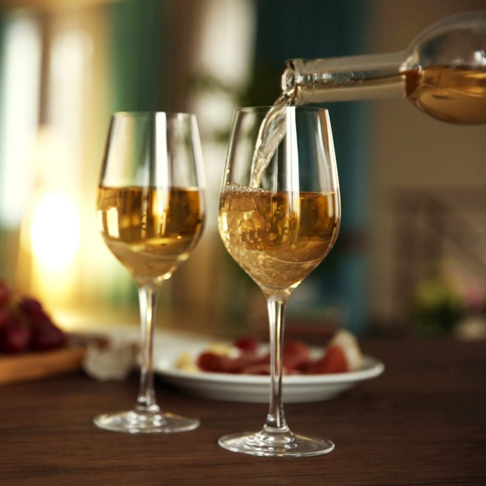 Pouring white wine from bottle into the wineglass on the table over blurred background