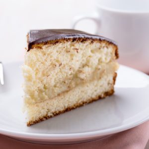 Homemade boston cream pie, piece of cake filled with a custard and frosted with chocolate;
