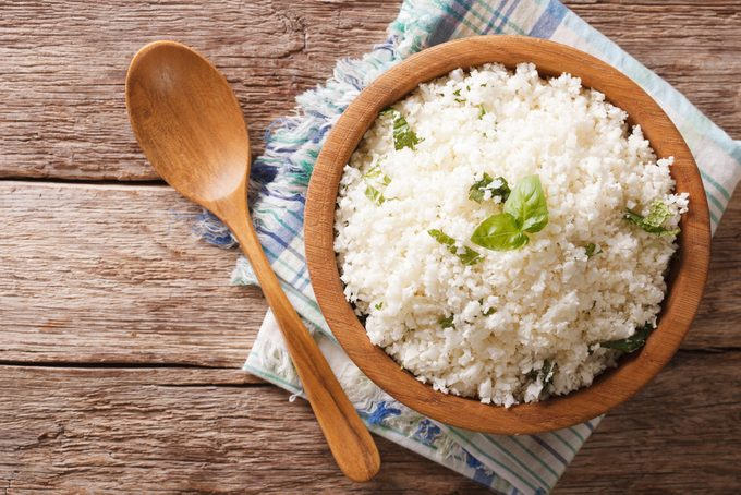 Cauliflower rice with basil close up in a bowl on the table.