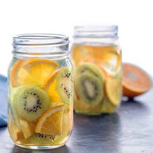 Infused water with kiwi and orange in jars, partly isolated