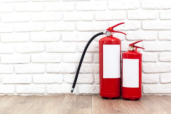 Fire extinguisher near white wall, ready for use