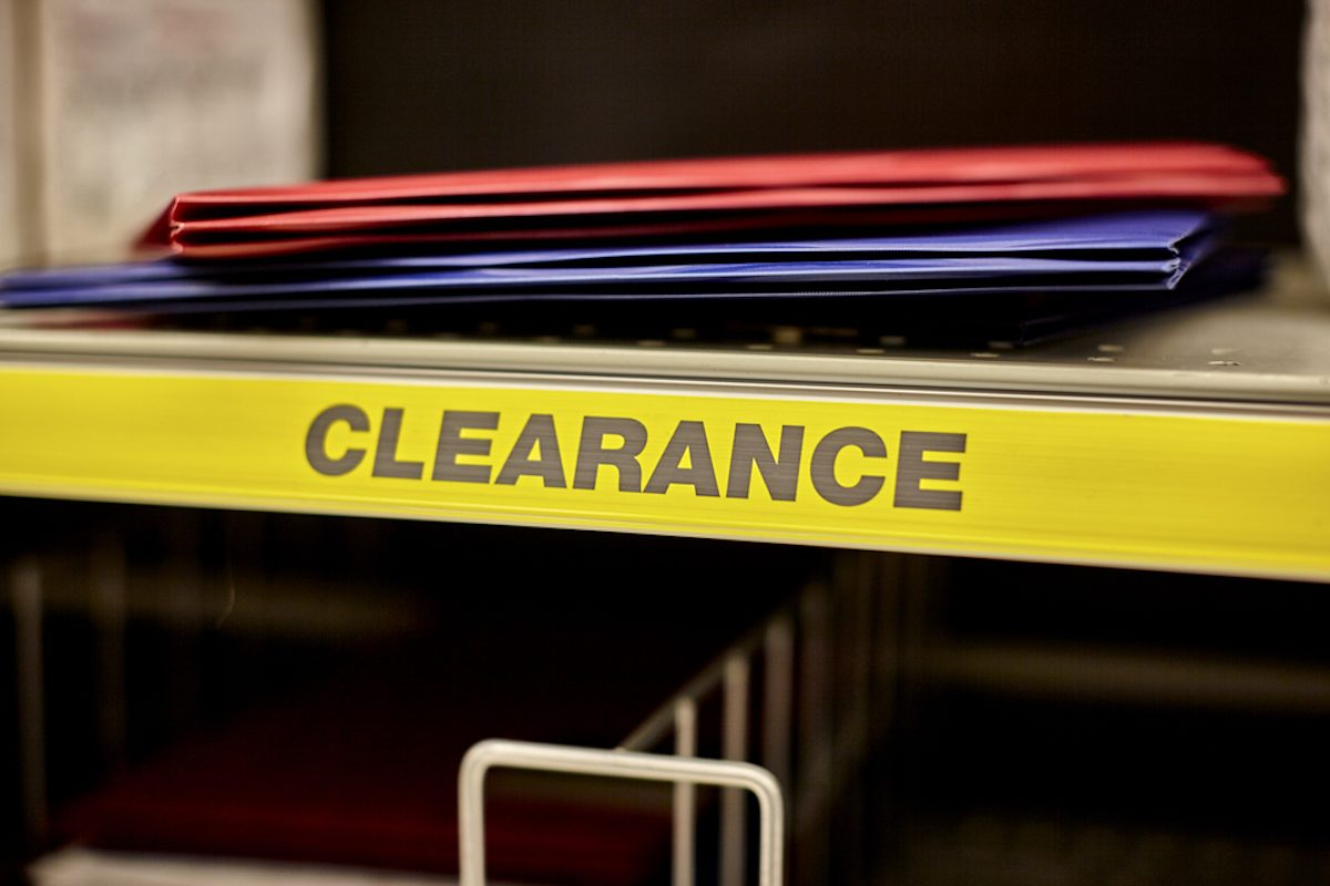 Red and blue folders on a clearance shelf in a retail store.