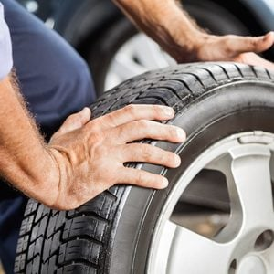 Mechanic Holding Car Tire At Garage.