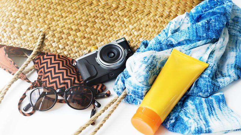 Sunblock, sunglasses, summer bag, beach trip, concept.