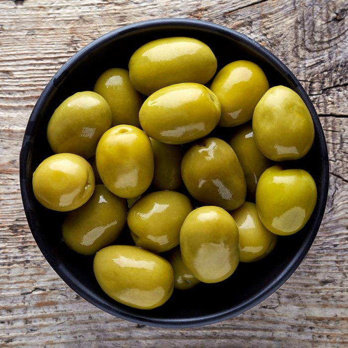 Bowl of pickled olives on wooden background