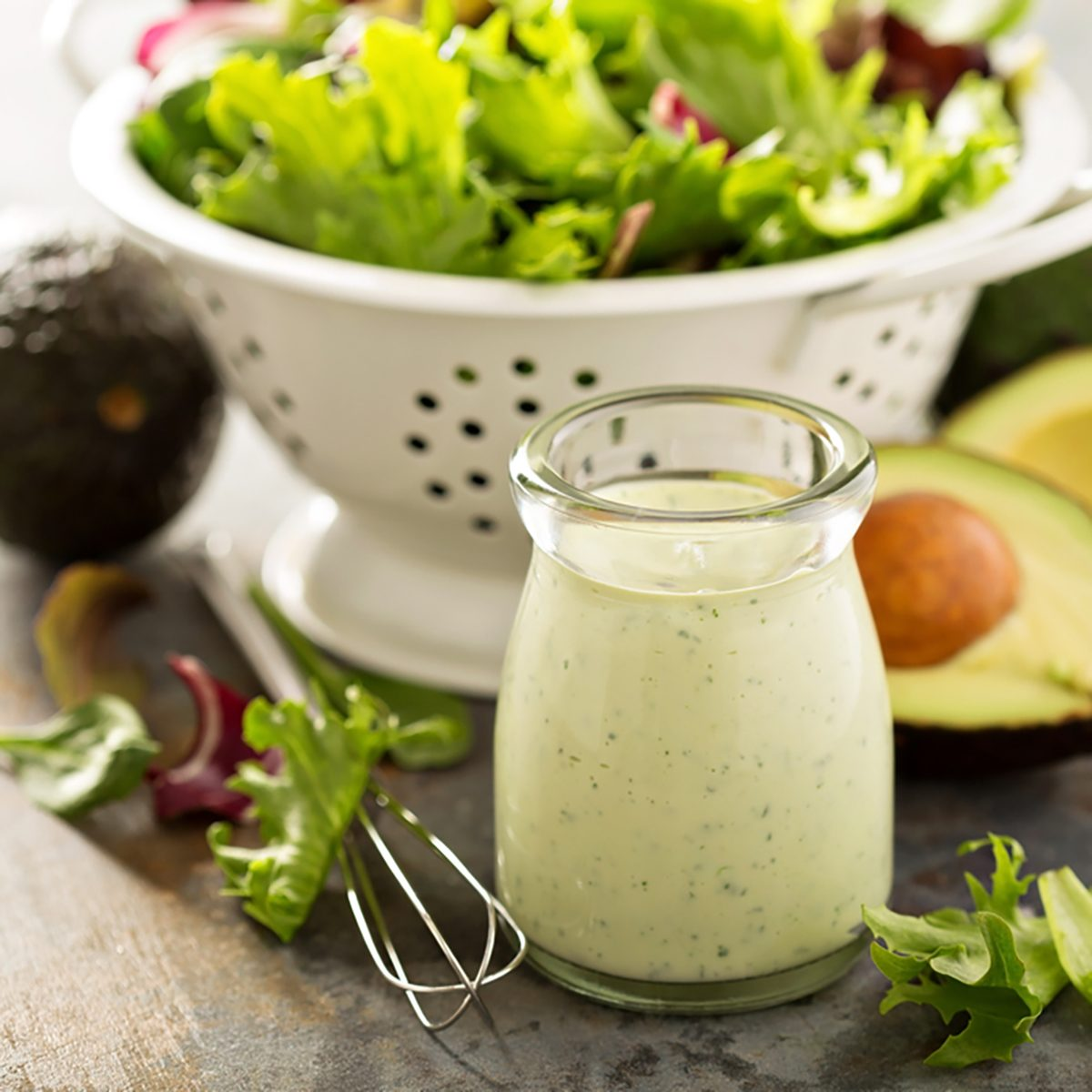 Avocado ranch dressing in small jar with salad leaves in a colander.