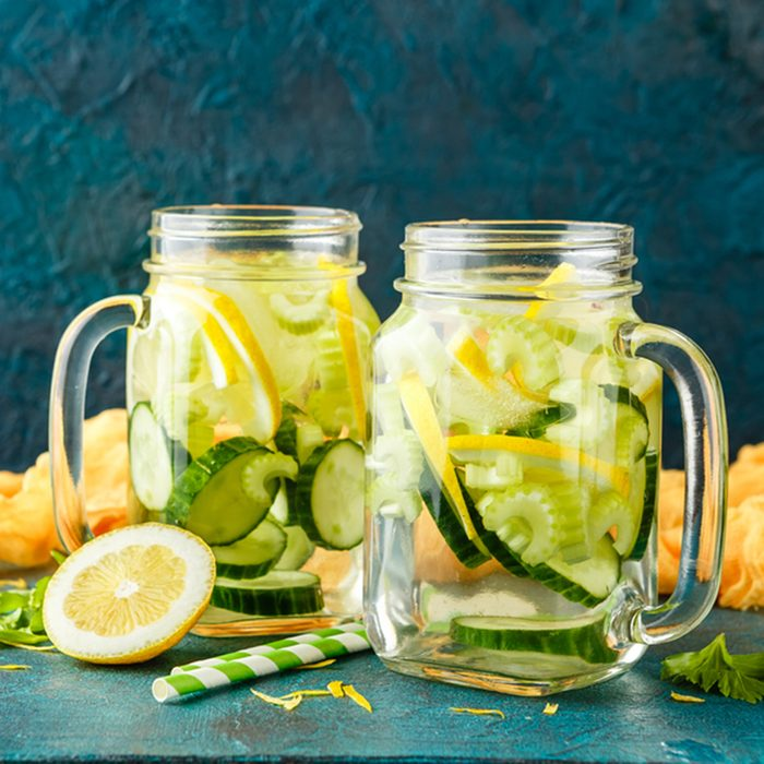 Detox infused hydrating water with cucumber, lemon and celery in glass jars on a turquoise background