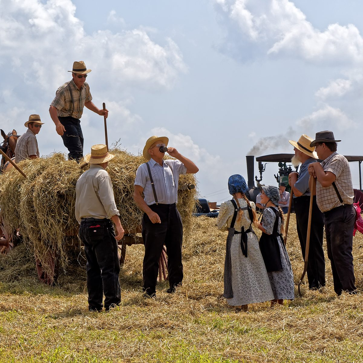 Two Mennonite girls take water to the hay crew