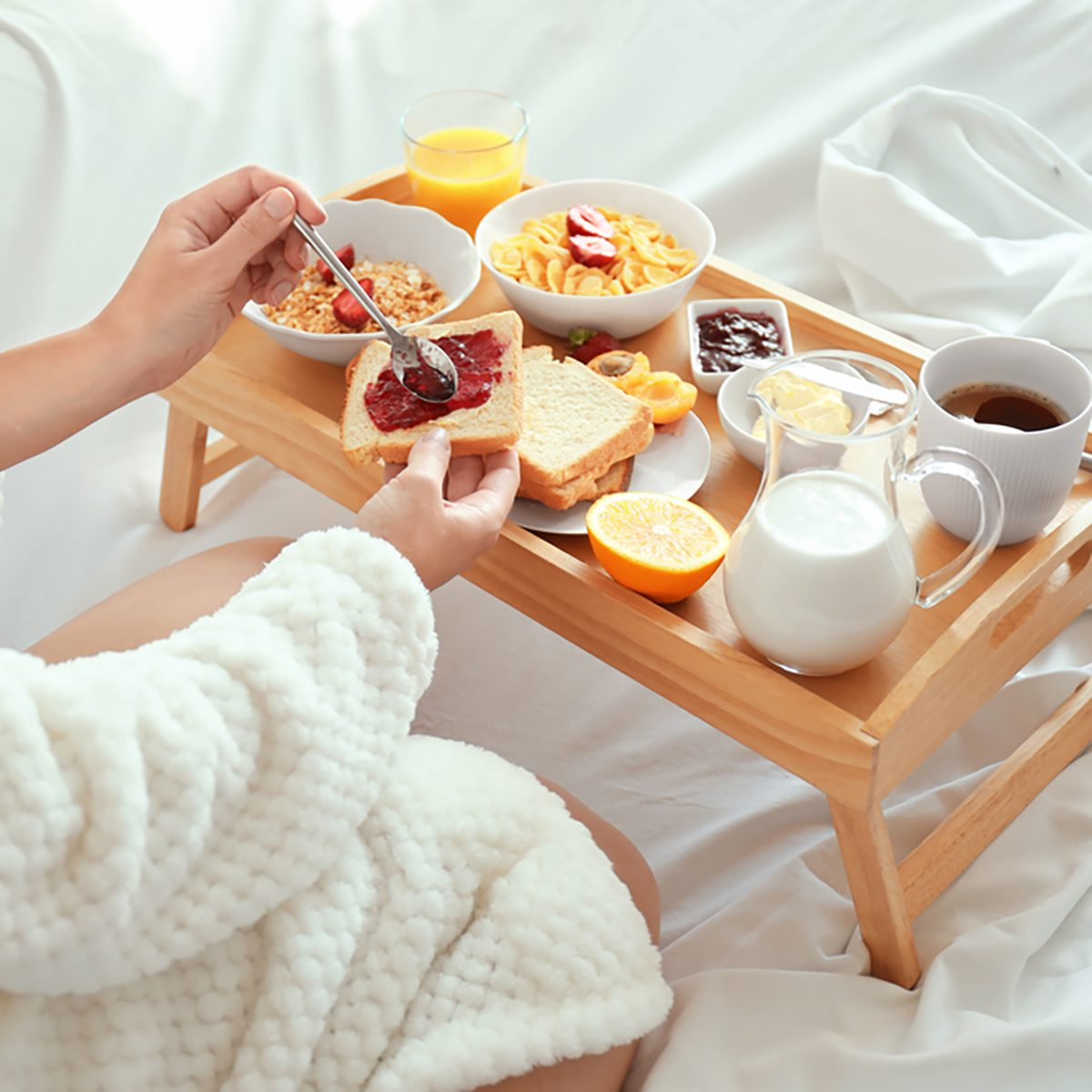 Young beautiful woman having breakfast on bed
