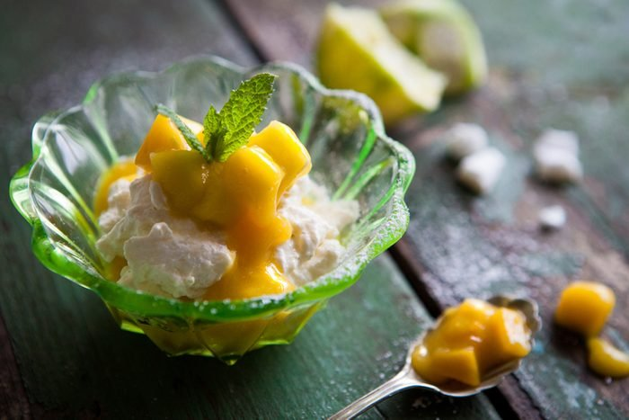 Fresh mango and lime syllabub served in a dainty emerald green glass dessert dish garnished with mint and icing sugar on distressed green wooden work surface