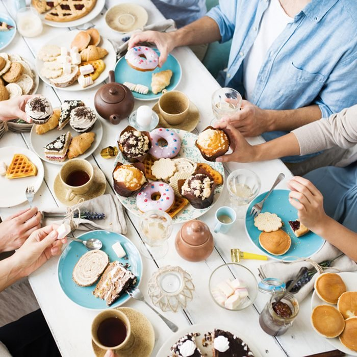 Friends gathered for birthday celebration having fresh homemade puffs and pastry with tea by served table