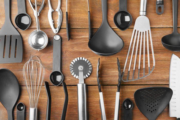 Various kitchen utensils on wooden background