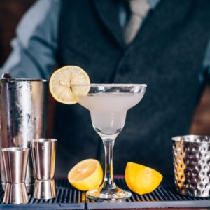professional bartender preparing tequila margarita with lime and lemon