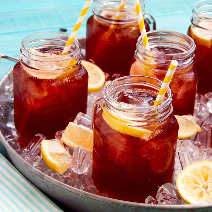 Mason jar mugs filled with iced tea and fresh lemon