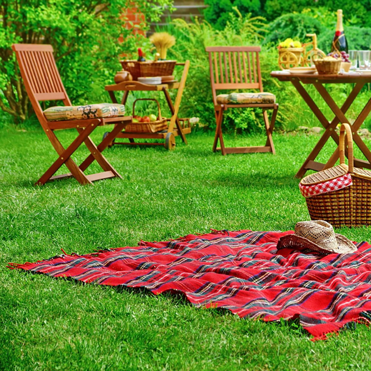Closeup Of Red Picnic Blanket With Cowboy Straw Hat And Basket Or Hamper