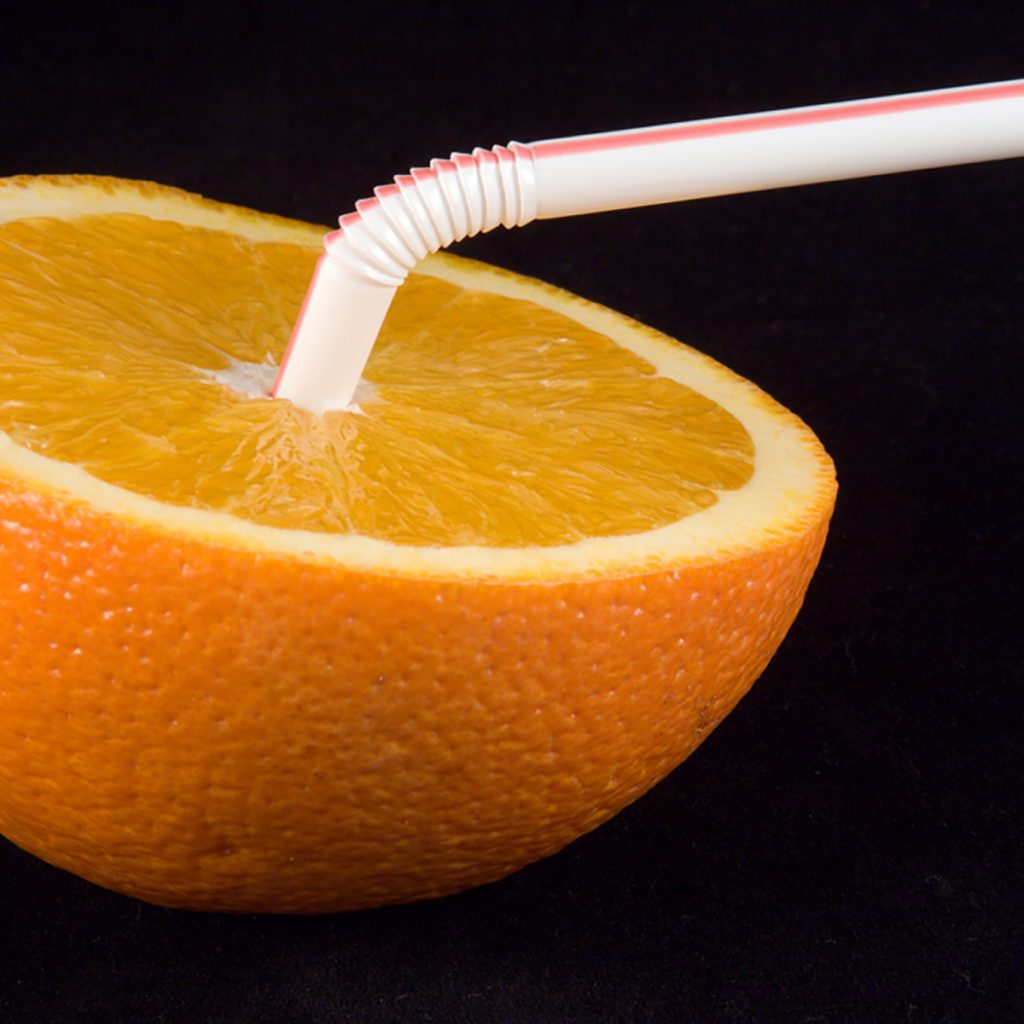 Orange half with straw inserted, on a black background.; Shutterstock ID 2434912; Job (TFH, TOH, RD, BNB, CWM, CM): Taste of Home