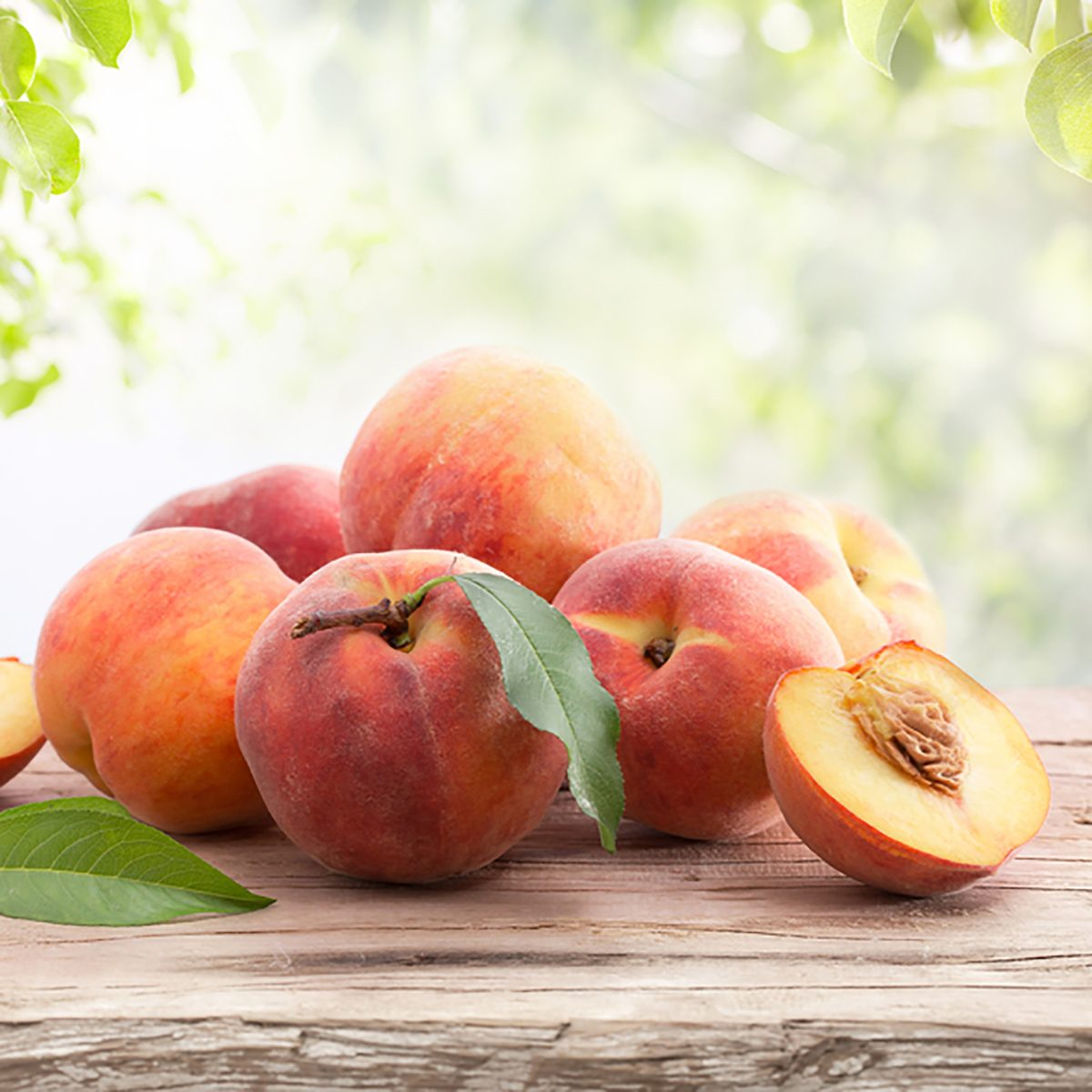 Ripe peaches with leaves on a wooden board on a background of green leaves; Shutterstock ID 682256068