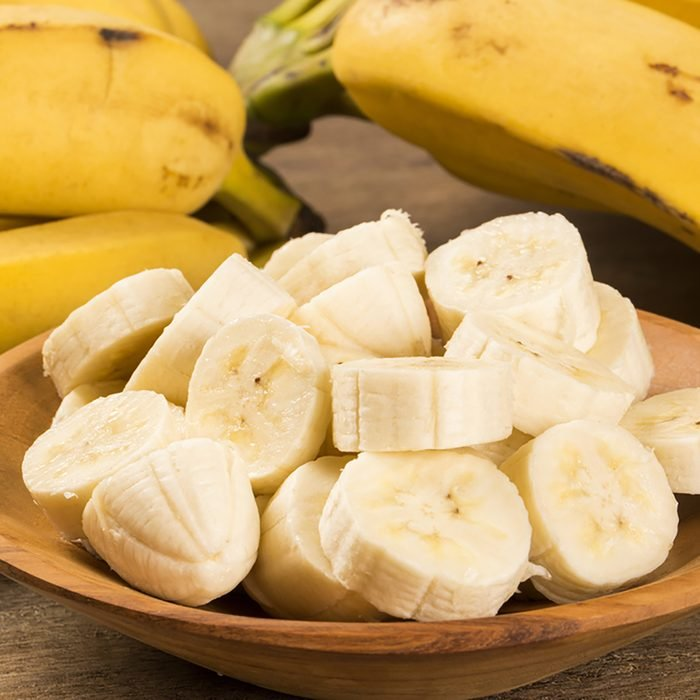 A banch of bananas and a sliced banana in a pot over a table.; Shutterstock ID 244685272; Job (TFH, TOH, RD, BNB, CWM, CM): Taste of Home