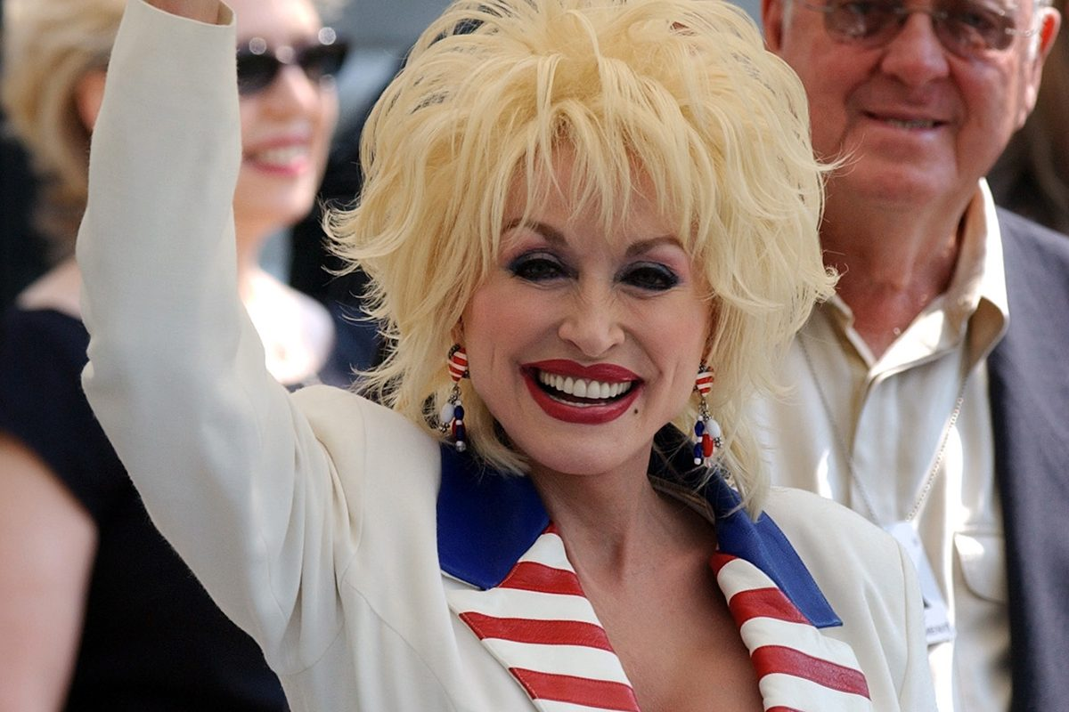 Dolly Parton waves to the cameras as President Bush departs from the White House