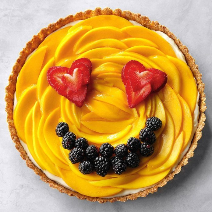 A mango pie with strawberry eyes and a blackberry mouth.