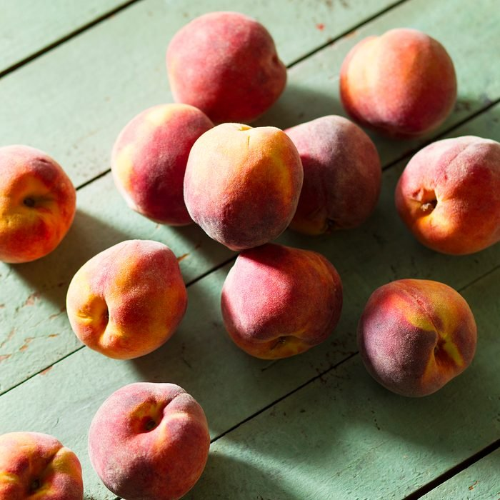 Fresh Peaches On Green Wood Surface