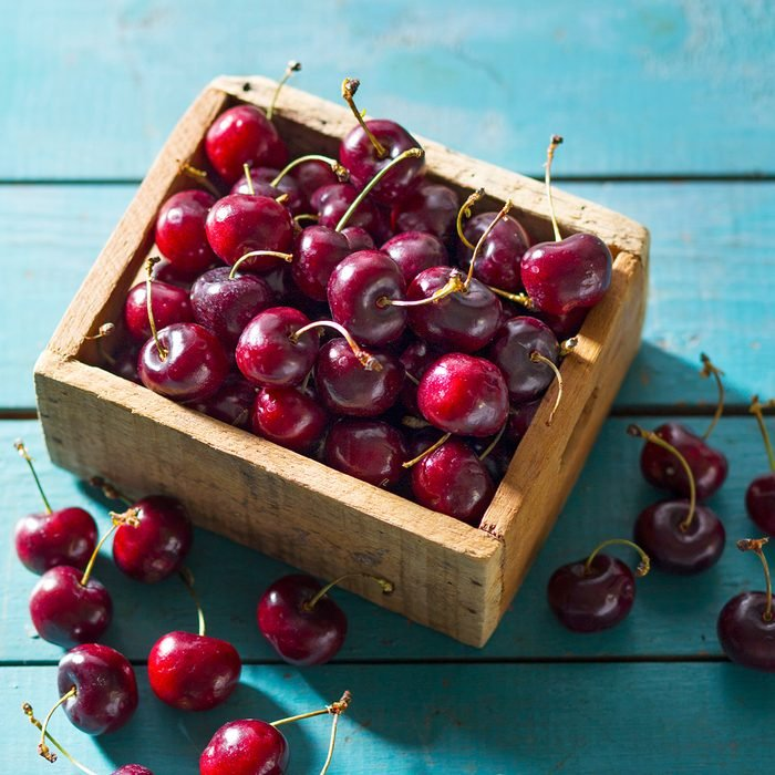 Fresh Bing Cherries In Wooden Box On Blue Wood Surface