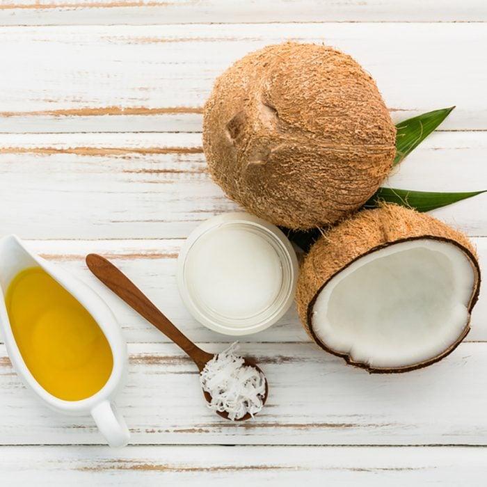 Coco com óleo de coco no fundo da mesa de madeira branca.