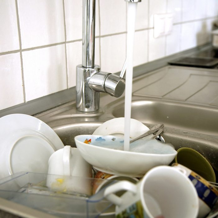 Pile of dirty dishes in the metal sink and pouring tap water.