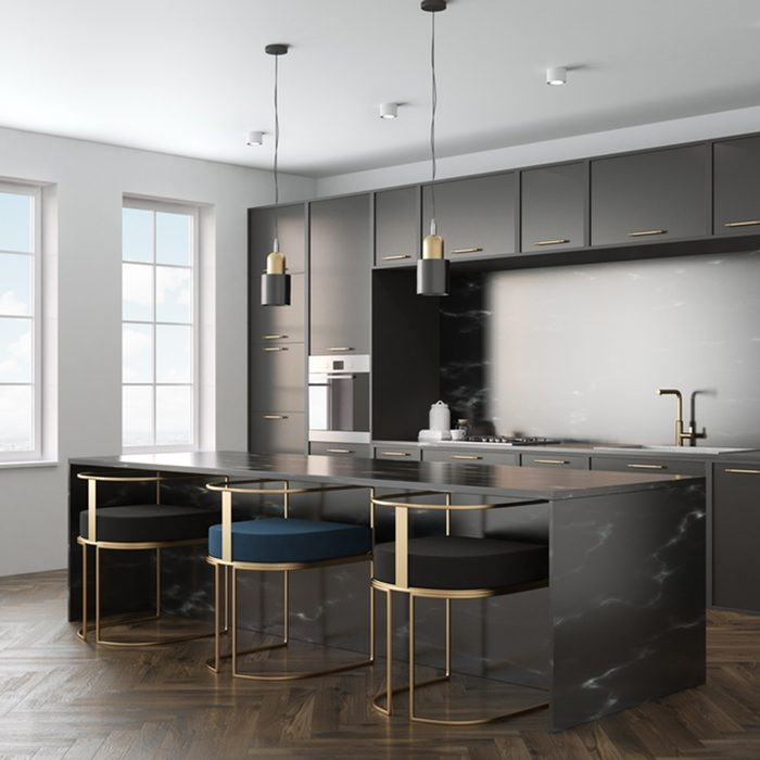 Kitchen interior with a wooden floor, black marble countertops and black cupboards with built in appliances.