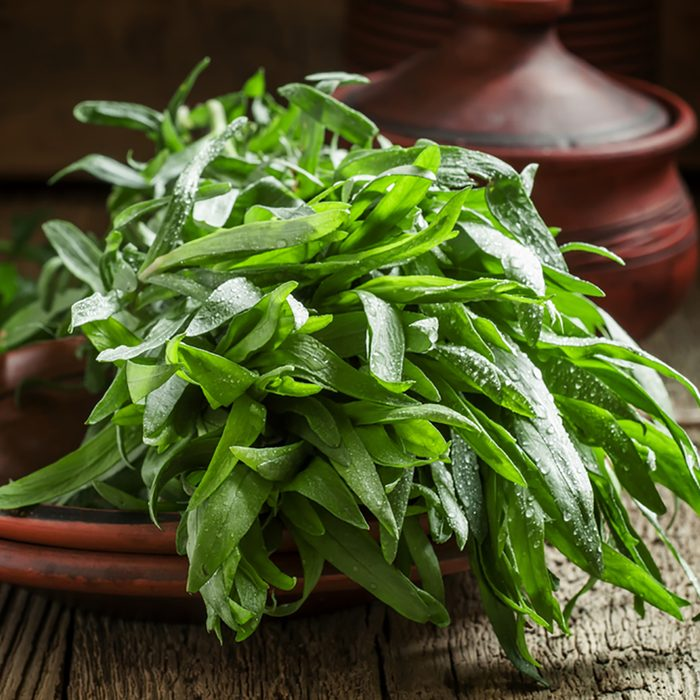 Fresh green tarragon in a beam in an earthenware pot on the old wooden background in rustic style, selective focus; Shutterstock ID 398503810