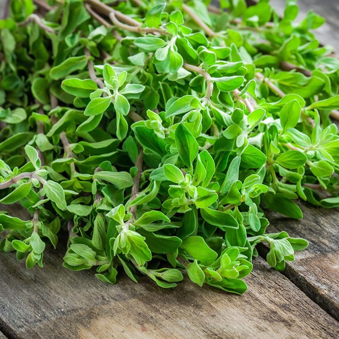 fresh raw green herb marjoram on a wooden rustic table; Shutterstock ID 266364122