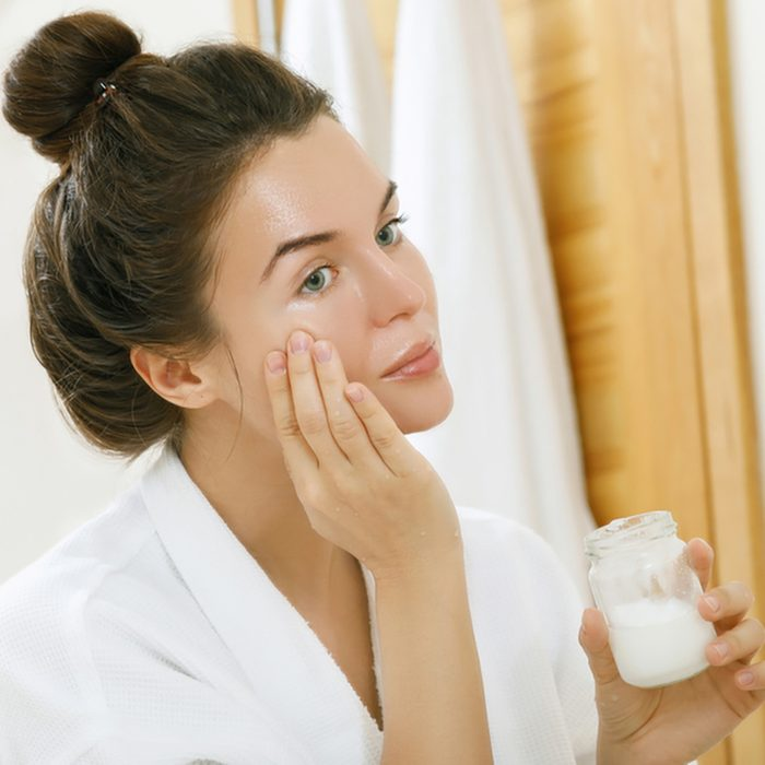 Mulher está hidratando sua pele com um óleo de coco