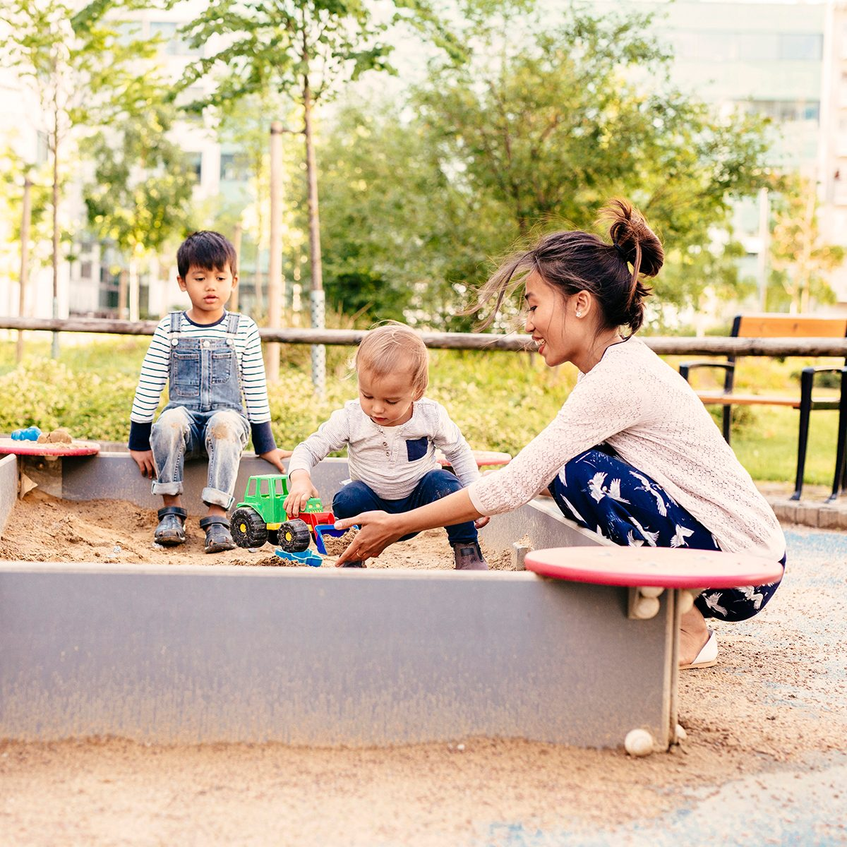 Mother playing with sons (2-3, 4-5) in sandbox