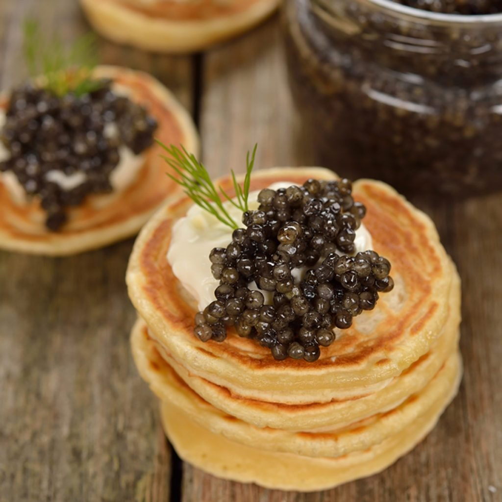 Mini pancakes with black caviar on a wooden background; Shutterstock ID 351283835