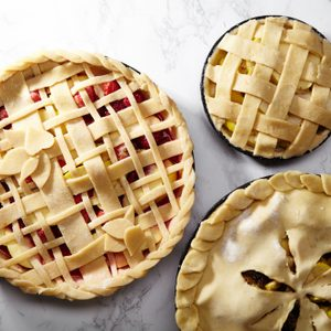 Pie crust design ideas - various ways of pie decoration with lattice and leaves. Apple, strawberry and raspberry pies uncooked on white marble table.