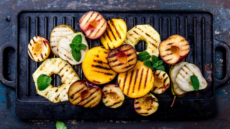 Grill fruits - pineapple, peaches, plums, avocado, pear on black cast iron grill board