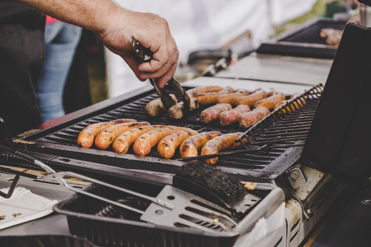 Grilling delicious juicy meat sausages on big grill outdoor.;