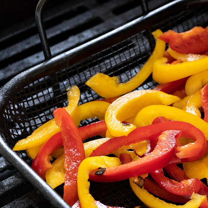 Close up on raw yellow and red bell peppers for fajitas, in a barbecue grill basket