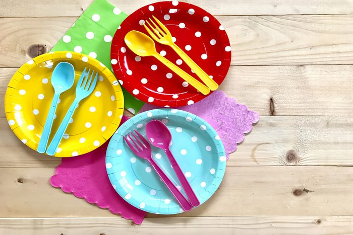 Colorful polka dot paper plate, plastic spoon & fork, napkin on wooden board background.
