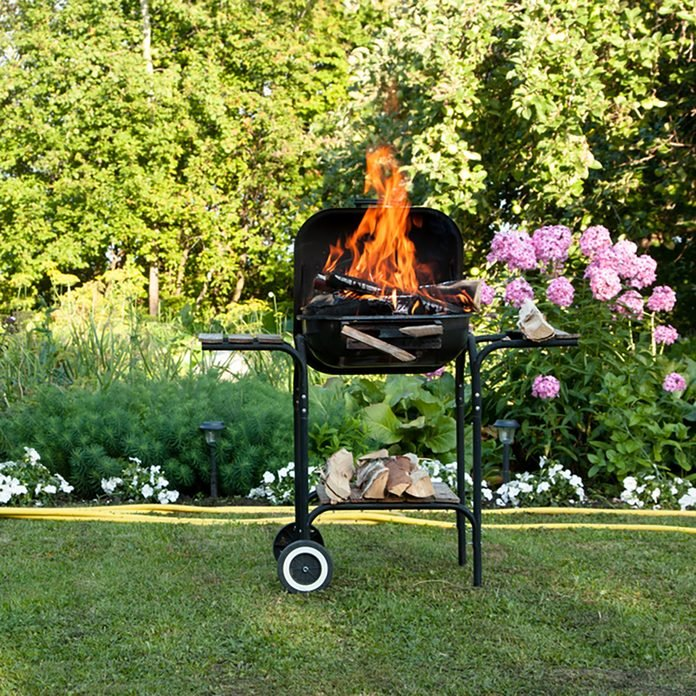 grilling safety Flames burning in a barbecue standing in a pretty garden as the coals are prepared for grilling an array of meat for a lunchtime cookout;