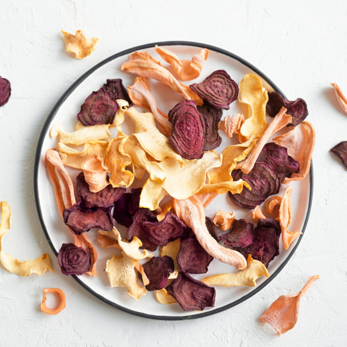 Various vegetable chips on white background, copy space. Assorted dehydrated beetroot, carrot, pumpkin vegetable chips - healthy vegan snack.; Shutterstock ID 1155178324; Job (TFH, TOH, RD, BNB, CWM, CM): TOH