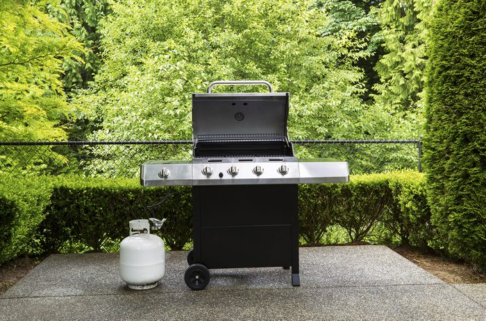 Horizontal photo of large barbeque cooker, with lid up, on concrete outdoor patio with woods background ; Shutterstock ID 144992224; Job (TFH, TOH, RD, BNB, CWM, CM): TOH How to Burp a Propane Tank