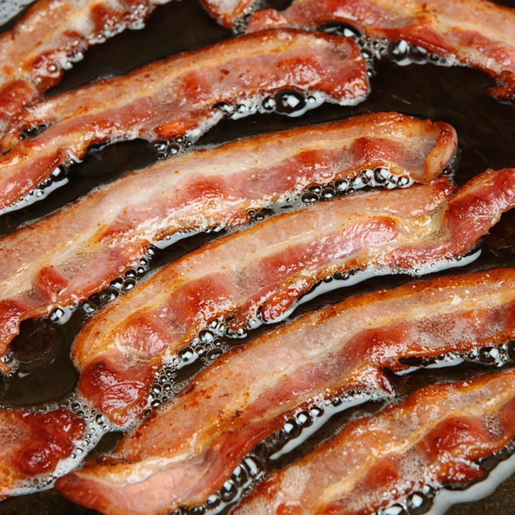 Bacon strips or rashers being cooked in frying pan