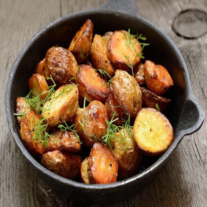Roasted potato in a frying pan on wooden table.