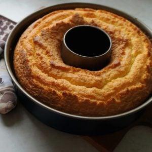 A freshly baked Bundt cake in the Bundt cake pan on a wooden board and two potholders/A freshly baked Bundt cake;
