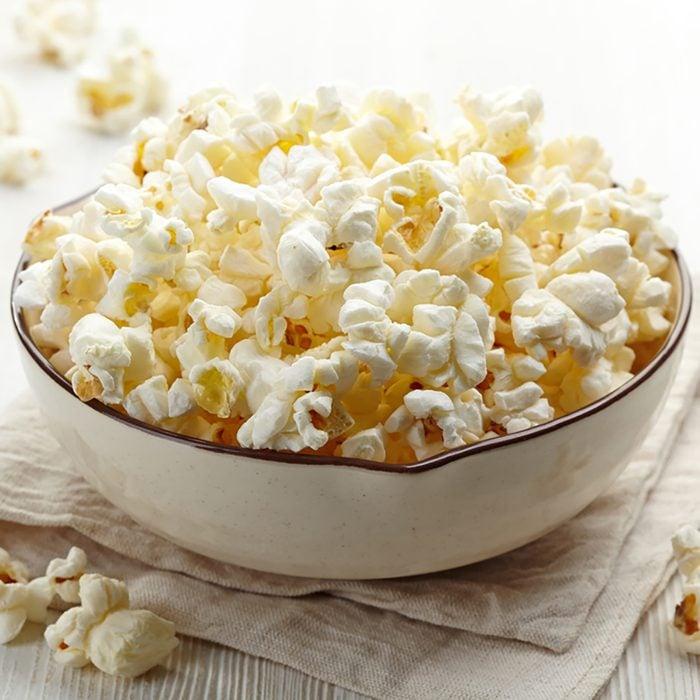 Bowl of fresh popcorn on white wooden background