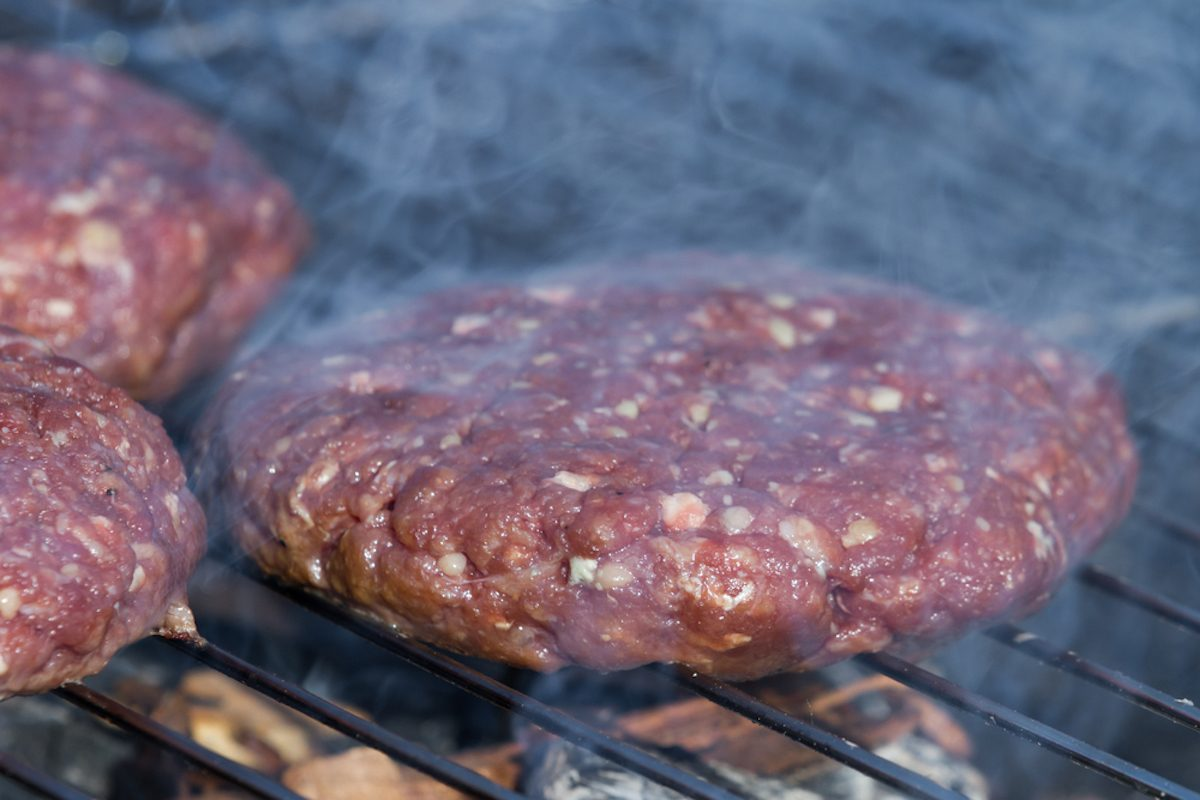 close up of hand formed hamburger patties on an outdoor grill with hickory wood chips for a smoky flavor