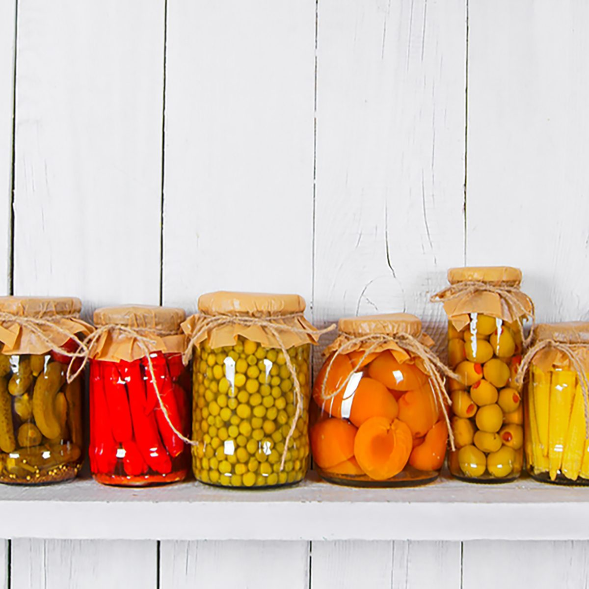 Preserved food in glass jars, on a wooden shelf. Various marinaded food