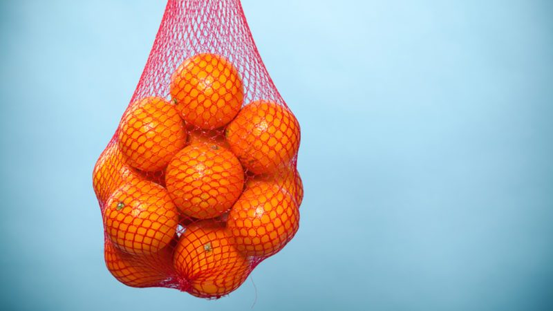Mesh bag of fresh oranges healthy tropical fruits from supermarket on blue.
